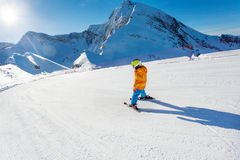 Boy in motion on ski-track skiing view from back Royalty Free Stock Image