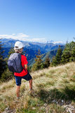 Boy in mountain using a smartphone. Young boy standing along a mountain path using a  smartphone for checking his gps position. Summer season, clear blue sky Royalty Free Stock Image