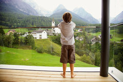 Boy in the mountains looking traditional swiss village Royalty Free Stock Photography