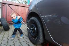 Boy mounted tires on a car. Stock Photos