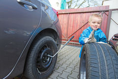 Boy mounted tires on a car. Stock Image