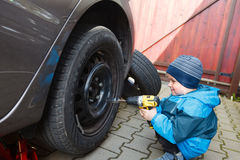 Boy mounted tires on a car. Royalty Free Stock Image