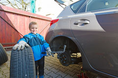 Boy mounted tires on a car. Royalty Free Stock Images