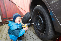 Boy mounted tires on a car. Stock Images