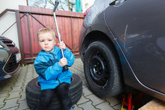 Boy mounted tires on a car. Stock Photo