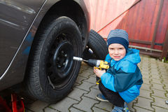 Boy mounted tires on a car. Royalty Free Stock Photography