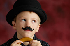 Boy with moustache and bowler. Funny young boy dressed as Charlie Chaplin with bowler hat, moustache and walking stock or cane Stock Photography