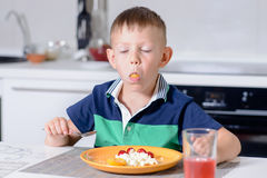 Boy with Mouth Full Eating Cheese and Fruit Stock Images
