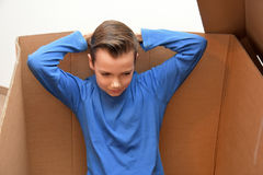 Boy in moving box. Boy sitting in an empty moving box stock photo