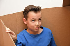 Boy in moving box. Boy sitting in an empty moving box royalty free stock image