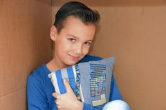 Boy in moving box. Boy sitting in an empty moving box stock image