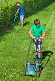 Boy mowing the lawn with man trimming at the edges. Boy mowing the lawn and men trimming the edges - summer activities around the house stock image