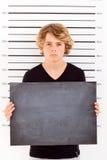 Boy mug shot. Teenage boy holding a blackboard taking criminal mug shot Stock Photography