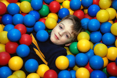 Boy in multi-coloured balls Stock Photo