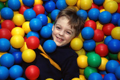 Boy in multi-coloured balls Royalty Free Stock Photo