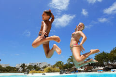 Boy with mum jumping into pool smiling Royalty Free Stock Photography