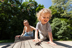 Boy and mum playing with bubbles Stock Photo