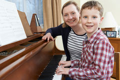 Boy With Music Teacher Having Lesson At Piano Stock Photography