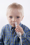 Boy and nasal aspirator. Young boy using nasal aspirator, mucus suction Royalty Free Stock Photography