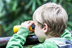 Boy in the the nature looking through binoculars. Young boy in the the nature looking through binoculars Stock Image