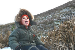 Boy on nature in winter. Boy on the nature of language catches snowflakes stock image