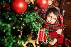 Boy near a Christmas tree. Family celebration of the New Year. Boy near a Christmas tree. Giving gifts. Holiday and fun stock photography