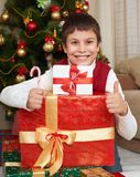 Boy near christmas tree and gift boxes, happy holiday and winter celebration, dressed in red Royalty Free Stock Image