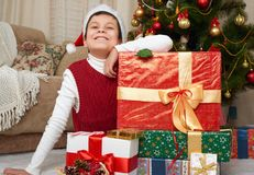 Boy near christmas tree and gift boxes, happy holiday and winter celebration, dressed in red Stock Images