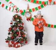 Boy near a Christmas tree on a white background. Boy near a Christmas tree on a white background Royalty Free Stock Photos
