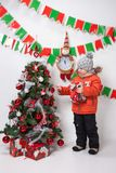 Boy near a Christmas tree on a white background. Boy near a Christmas tree on a white background Royalty Free Stock Image