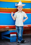 Boy near colorful boat. Portrait of little boy standing near traditional colorful Maltese boat Stock Photo