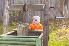 Boy near draw-well Royalty Free Stock Photography