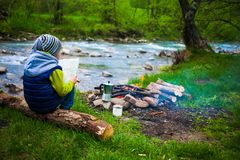 The boy near the fire. The boy sits on the Bank of the river near the bonfire and holds the map, near the fire is a mug and a coffee maker, a child sitting on a Stock Photography