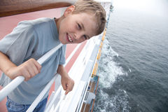Boy near handrails on deck of ship. Little boy near handrails on deck of big passenger ship Royalty Free Stock Images