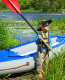 Boy near a kayak on the river Royalty Free Stock Image