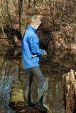 Boy near log fishing at shallow pond Royalty Free Stock Image