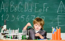Boy near microscope and test tubes school classroom. Knowledge concept. Knowledge day. Kid study biology chemistry stock image