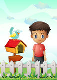 A boy near the pethouse with a bird and a wooden arrowboard Stock Photo