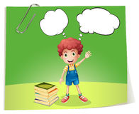 A boy near a pile of books with empty callouts Royalty Free Stock Photo