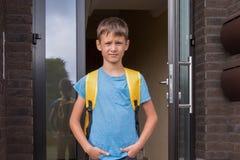 Boy near residential apartment house ready to go to school royalty free stock photos