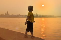 Boy near the river looks at a beautiful sunset. Boy looks at the sunset royalty free stock images