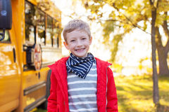 Boy near schoolbus. Cheerful little boy standing near schoolbus ready to go to school, back to school concept Royalty Free Stock Images