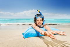 Boy the sea beach in scuba mask on matrass. Boy near the sea lay on the matrass stretching arms and smile in scuba mask royalty free stock image