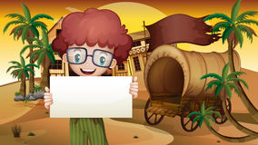 A boy near the wagon holding an empty signboard Royalty Free Stock Photography