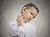 Boy with neck pain. Neck pain. Portrait stressed unhappy child boy with back pain, after long school hours studying isolated grey wall background. Negative human Royalty Free Stock Images