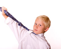 Boy With Necktie Pretending to be Grown-Up. Young Blond Boy Pretending to be Grown-Up Shows Emotion with Men's Tie.  Boy is wearing a man's white dress shirt and Royalty Free Stock Photography