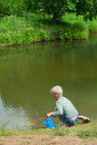 The boy with a net on the bank of lake. Summer royalty free stock photos