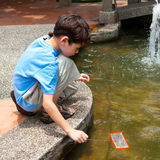 Boy with a net by the fish pond Royalty Free Stock Photography