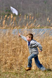 Boy With Net Running Royalty Free Stock Photography