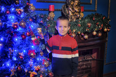 The boy next to a glowing blue Christmas tree and fireplace Royalty Free Stock Images